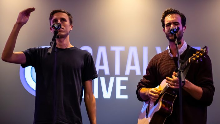 Harry and Chris singing and playing guitar in front of a projected Catalyst Live logo
