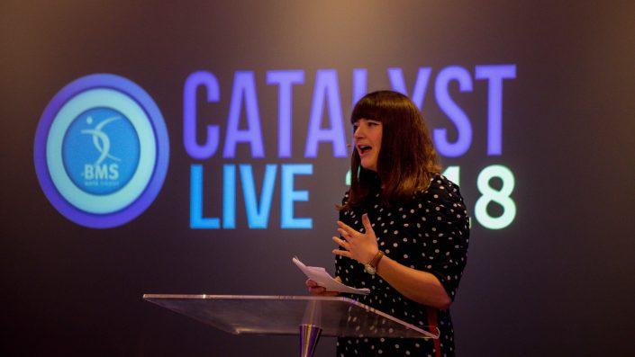 Helen Coffey speaking in front of an illuminated Catalyst Live logo