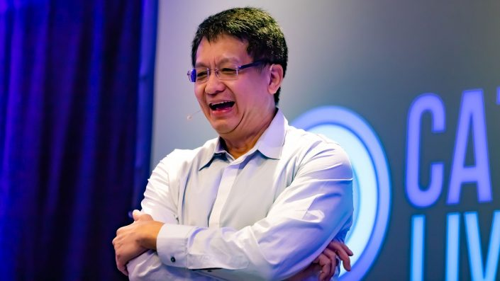Close up of Ron Choong laughing in front of the Catalyst Live logo