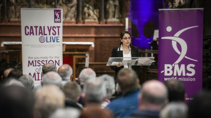 Wide shot of Rula Mansour speaking at a lectern in a church with audience in the foreground